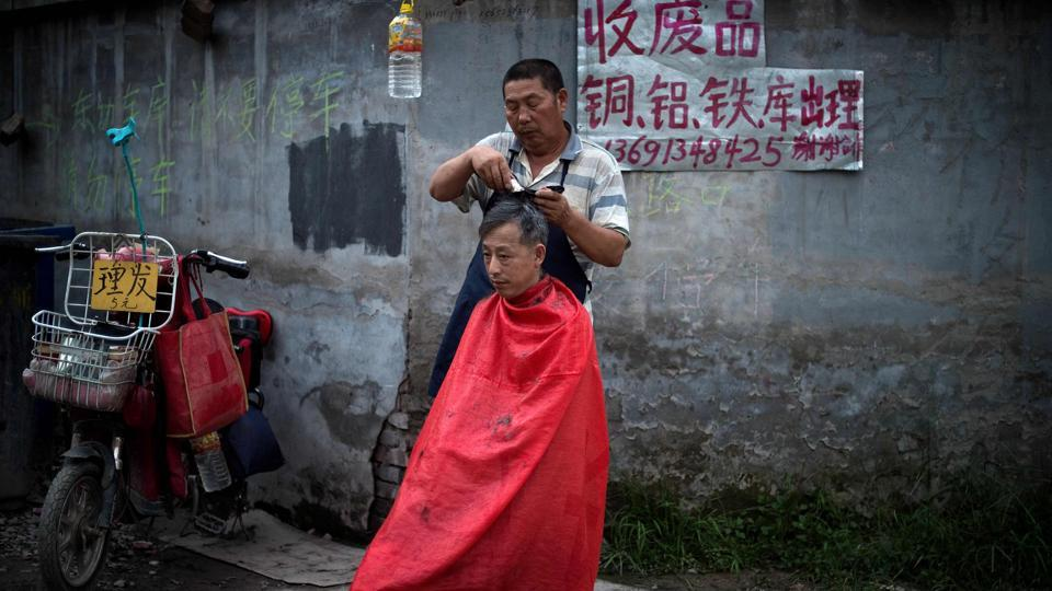 A man gets a haircut on a street  in Zhongguancun. 'Some of us used to make 6,000 yuan a month as Didi (ride-share company) drivers. But the government said migrants can't drive Didi, so we had to find other work,' said Yang Qiang. (Nicolas Asfouri / AFP)