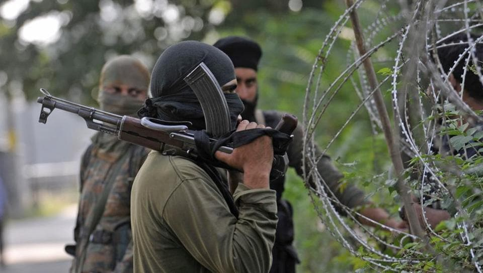 Policemen stand guard during a search operation in Srinagar after three militants were killed in a gunfight with security forces in Tral.