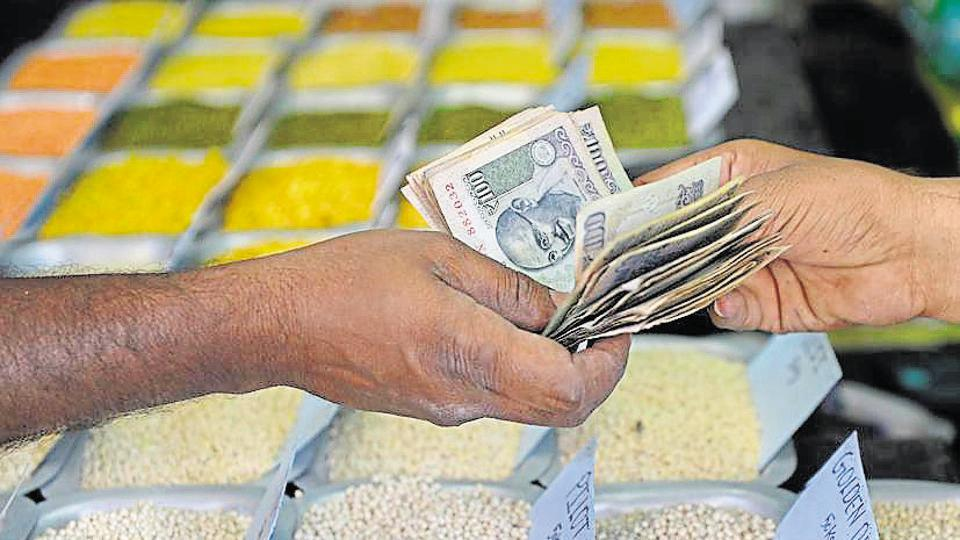 A customer hands over cash to a food grain merchant at a wholesale trading shop in Bangalore.