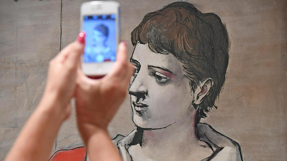 A woman takes a picture of Picasso's Saltimbanque aux bras croises, oil on canvas, 1923, during the preview of Picasso exhibition in Rome on Thursday.