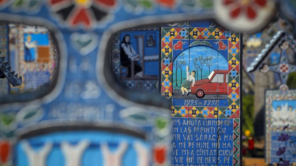 The story of a three-year-old child who was run over by a car is depicted on her cross in the Merry Cemetery. Another tells the tale of a 38-year-old man who had a 'merciless death' that snatched him from his wife and two daughters. (Vadim Ghirda / AP)