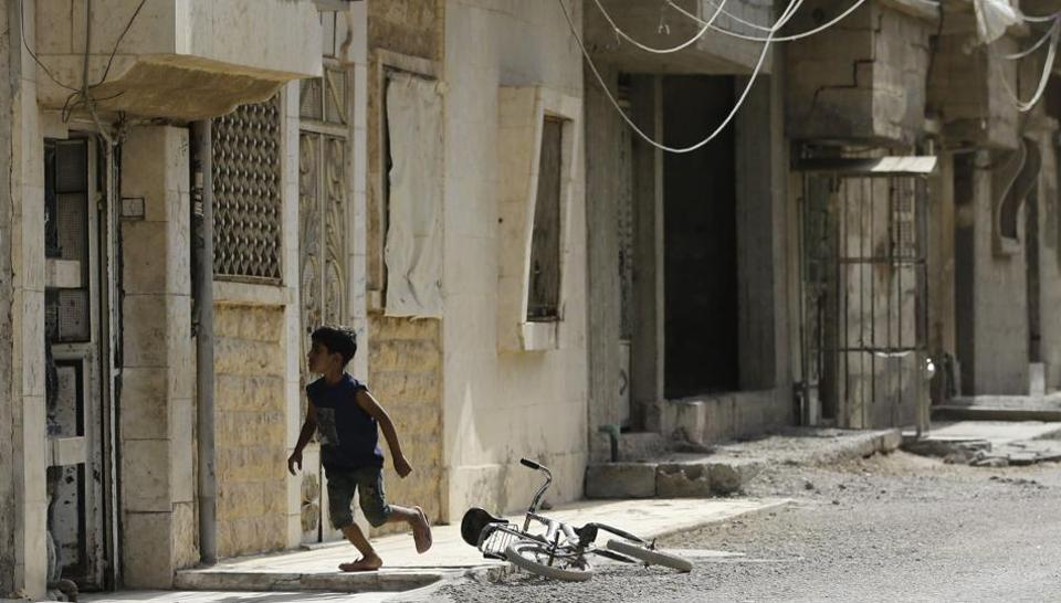 A Syrian boy runs near his bicycle in the eastern Syrian city of Deir Ezzor on September 21 as Syrian government forces continue to press forward with Russian air cover in the offensive against Islamic State group jihadists across the province.
