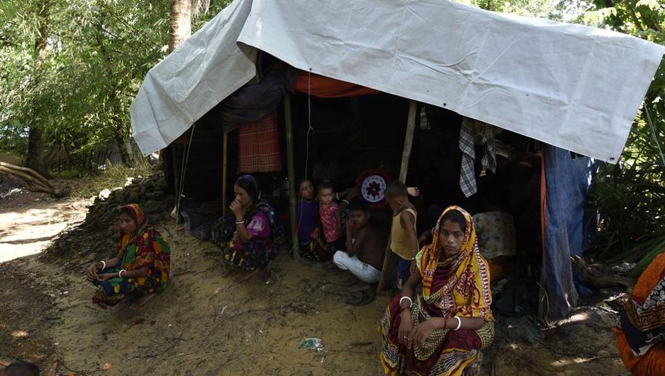In this photograph taken on September 21, 2017 Hindu refugees from Myanmar seat outside their makeshift shelter in a Hindu village near the Bangladeshi town of Kutupalong.