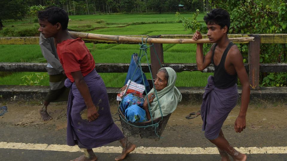 (FILES) This file photo taken on September 19, 2017 shows Rohingya Muslim refugees carrying an elderly woman along a road near Balukhali refugee camp near the Bangladeshi district of Ukhia.