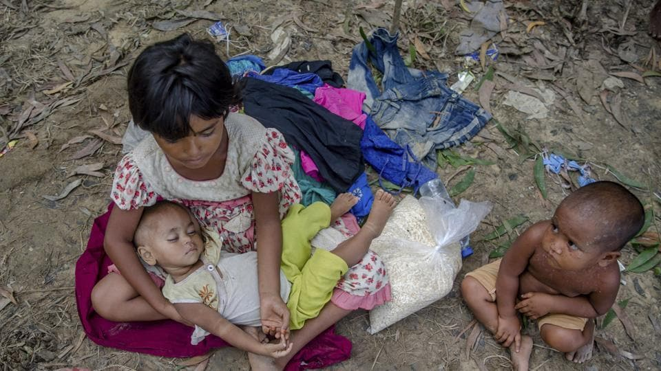 Asmat Ara, a Rohingya Muslim girl who crossed over from Myanmar into Bangladesh, holds his brother Musharraf as her younger sister Zanooba sits beside her by the side of a road waiting for aid from passersby near Taiy Khali refugee camp, Bangladesh.