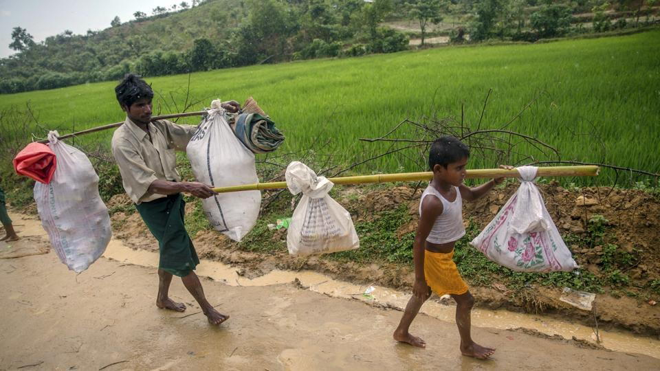 A Rohingya Muslim boy, Mohammad Arafat, carries his belongings and walks with his father Zahoor Hussain as they arrive at Taiy Khali refugee camp, Bangladesh, Thursday, September 21, 2017.