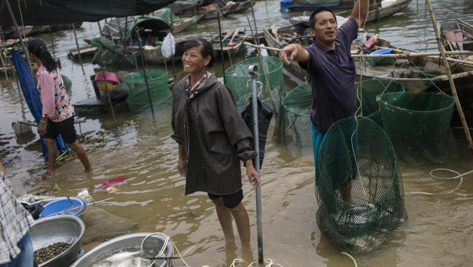 Lin Ziqiang, 43, and his wife, surnamed Chen, take their boat out to fish at sunrise every day, coming back to the shore next to a towering bridge at around 1 pm. Every evening, the couple sells their fresh catch at the market by the Beijiang River, making between 3,000 and 4,000 yuan (RS.29,879 and Rs.39,627 approx.) a month. (Fred Dufour / AFP)