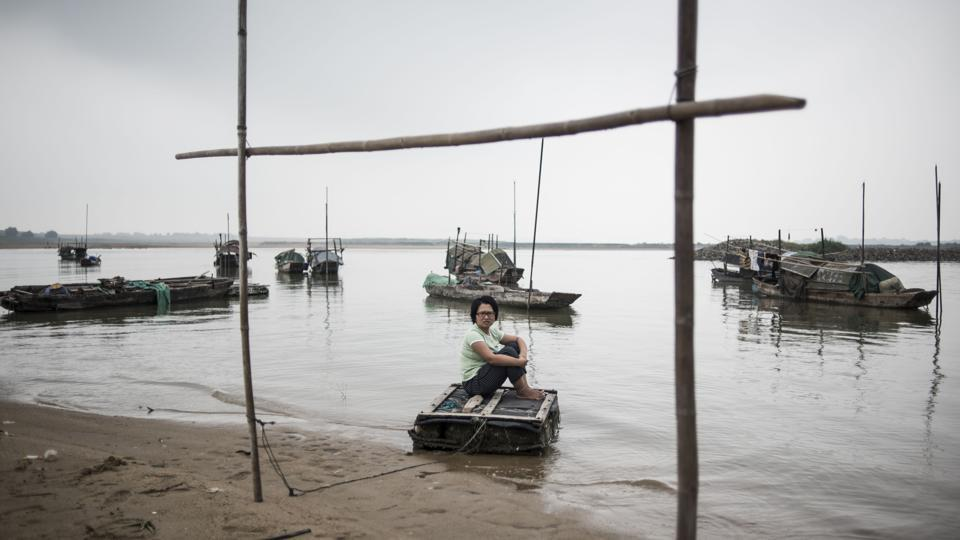 Along southern China's snaking rivers, an ancient fishing community that once lived and worked exclusively on the water has been finding its way to land. Wooden fishing boats, wispy nets and bamboo steering poles are typical of the traditions of the 'Tanka' -- the term for generations of rural Chinese who have eked out an aquatic existence. (Fred Dufour / AFP)