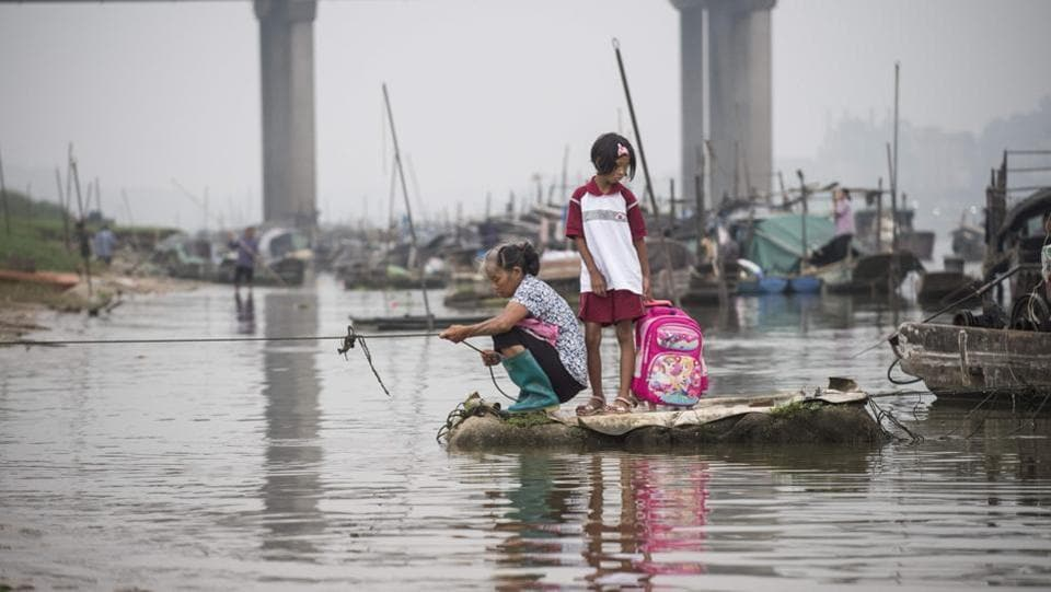 On a morning in Datang, an older woman in rubber boots squatted on a small bank as she pulled in a fishing line. Beside her, a girl stood in a red and white uniform, holding onto a pink Disney princess backpack. Jumping from a boat to the sandy shore, she began her walk to school. (Fred Dufour / AFP)