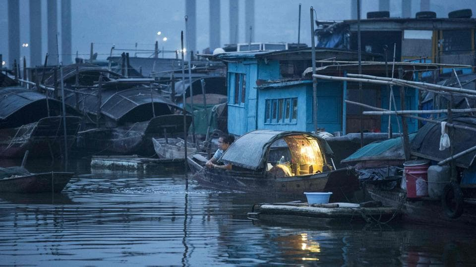 Boats are parked haphazardly along the shore, their decks packed with fishing equipment, blankets and sometimes people sleeping. Men and women in straw hats balance rods holding nets of carp on either end. (Fred Dufour / AFP)
