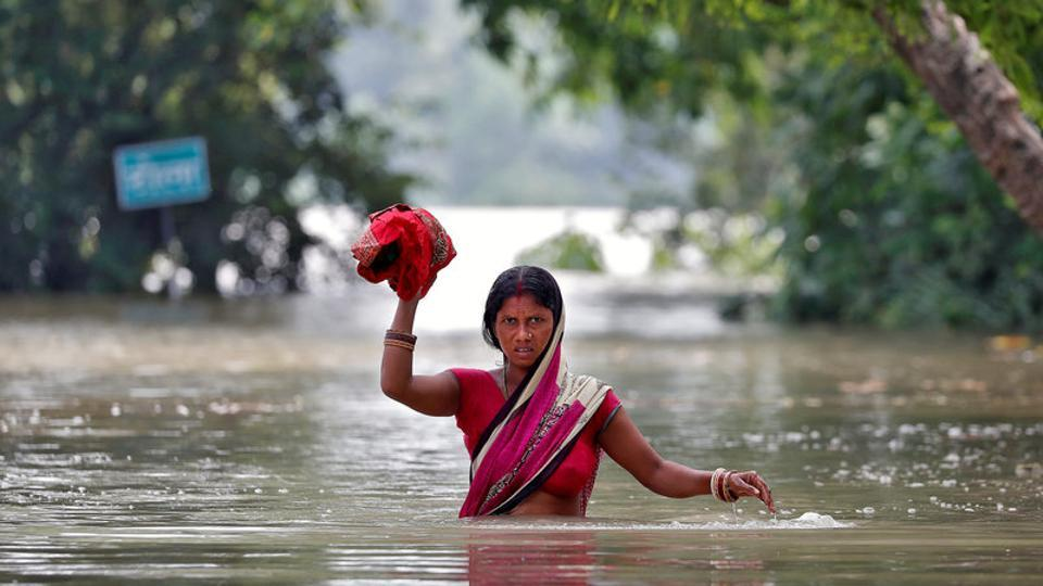 A woman wades through a flooded village in Bihar.