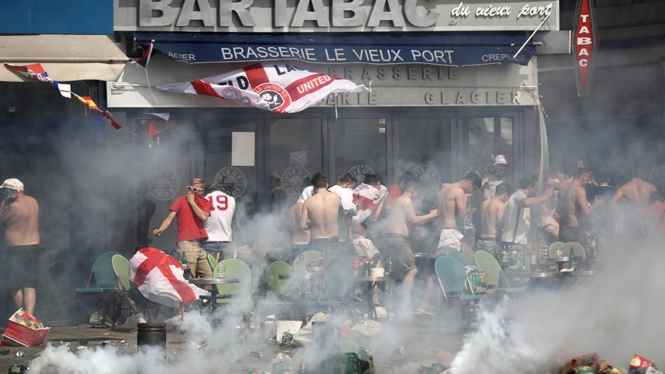 "MARSEILLE, FRANCE - JUNE 11: England fans react after police sprayed tear gas during clashes ahead of the game against Russia on June 11, 2016 in Marseille, France. Manchester United and Liverpool supporters travelling to Moscow for their teams' Champions League matches next week have been advised to expect a ""visible police presence"" amid fears of violence."