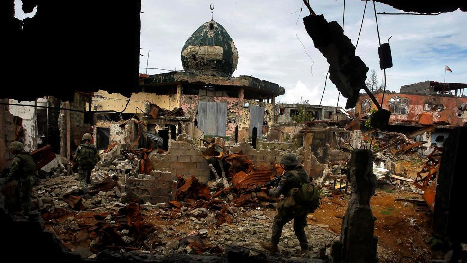 Philippine Marines patrol past damaged buildings as troops continue their assault against the pro-IS militant group in Marawi. Duterte warned he will use force or expand nationwide his declaration of martial law in the country's south if the anti-government protesters threatened public order. In May, he placed the southern third of the largely Roman Catholic nation under martial law to deal with a siege by pro-ISIS militants in southern Marawi that has dragged on for nearly four months. (Marconi Navales / REUTERS)