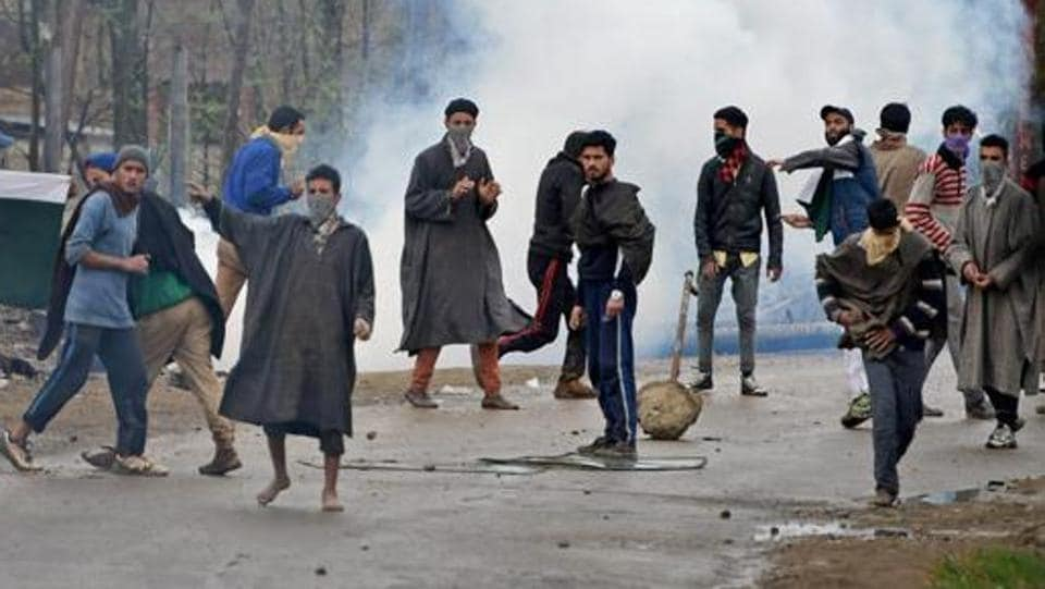 A group of youth pelt stones on security forces during an anti-militant operation at Durbugh village in Chadoora area of central Kashmir's Budgam district on Tuesday.