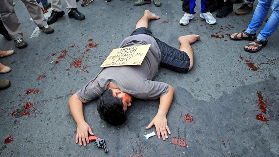 A protestor pretends to be dead to picture one of the victims of war on drugs of President Rodrigo Duterte during a National Day of Protest outside the Malacanang presidential palace in Manila. A note read 'Don't imitate it was mistaken identity'. Pro-Duterte followers also staged rallies in Manila. The rival demonstrations reflected deepening divisions sparked largely by the president's brutal anti-crime style. (Romeo Ranoco / REUTERS)