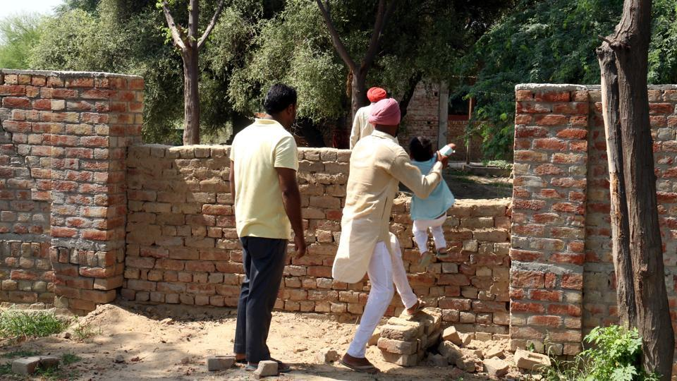 People from Scheduled Caste (Dalit) community crossing a wall to enter the separate cremation ground for them in Kot Guru village as no thoroughfare has been left for them except a detour through a dumping ground.