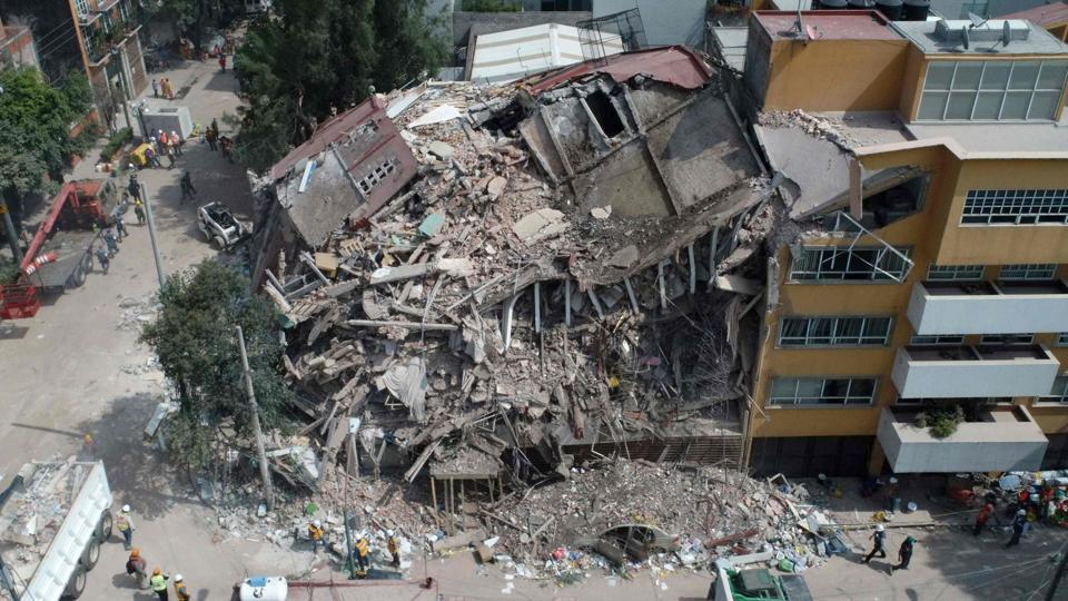 Aerial view of a flattened building in Mexico City taken on September 20, 2017 as the search for survivors continues two days after a strong quake hit central Mexico.