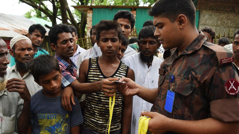 Rohingya refugee receive new ID card from a soldier at the entrance of the Bangladeshi government registration office at the refugee camp of Kutupalong near in Ukhia on September 22.