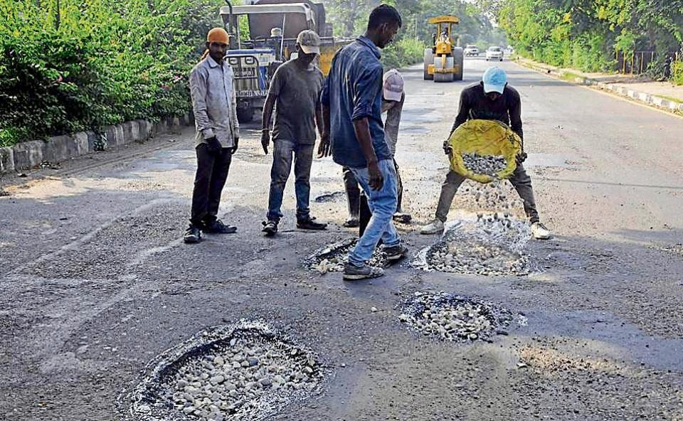 Workers filling potholes on the Sector 4-11 dividing road in Panchkula.