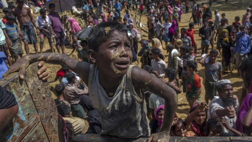 A Rohingya Muslim boy, who crossed over from Myanmar into Bangladesh, pleads with aid workers to give him a bag of rice near Balukhali refugee camp.