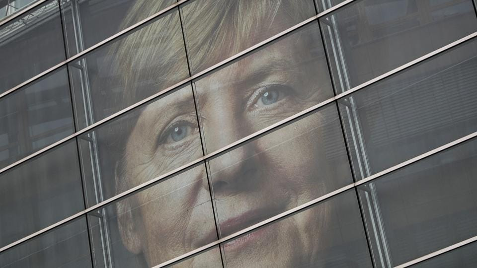 A picture of German Chancellor Angela Merkel can be seen behind the glass panes of the CDU headquarters in Berlin, Germany, on  September 23, 2017, one day ahead of the German federal elections.