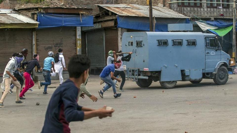 Kashmiri protester throws rocks and bricks at an armoured vehicle during a protest in Srinagar in May.