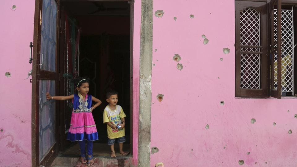 Children stand by the door to a house damaged by firing, allegedly from the Pakistan side of the border, near the International Border in Arnia village near, about 47 kilometers (30 miles) from Jammu, India.  Schools in the international border area have been closed and residents are moving to safer areas as firing continued in the region. India and Pakistan have a long history of bitter relations over Kashmir. They have fought two of their three wars over the region since they gained independence from British colonial rule in 1947.  (Channi Anand / AP)