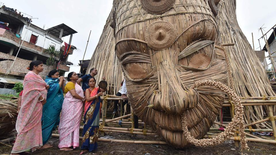 Devotees offer prayers to the head of a 100-foot bamboo idol of the Hindu deity Durga in Guwahati in honour of the Durga Puja festival.