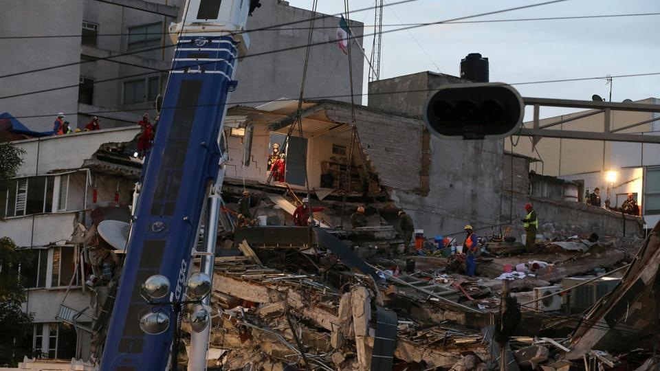 Members of rescue teams search for survivors in the rubble of a collapsed building after an earthquake in Mexico City.