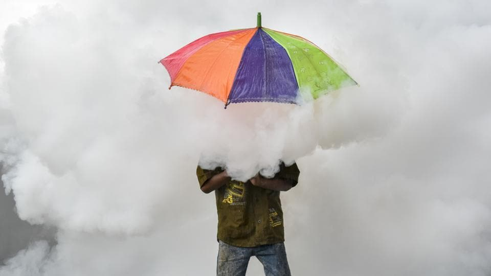 A child engulfed in plumes of smoke during a fumigation drive, feigns shelter under an umbrella at Sion in Mumbai. (Kunal Patil / Ht photo)