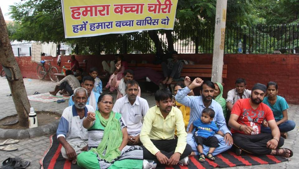 Family members of the newborn sitting on a dharna outside PGIMS on Saturday.