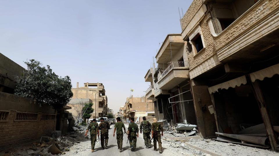 Members of the Syrian Democratic Forces walk in the former Islamic State (IS) stronghold of Raqa on September 22, 2017, as the Syrian fighters backed by US special forces battle to clear the last remaining jihadists holed up in the city.