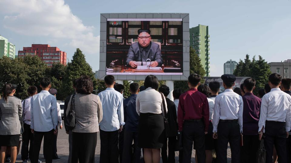 Spectators listen to a television news broadcast of a statement by North Korean leader Kim Jong-Un, before a public television screen outside the central railway station in Pyongyang on September 22, 2017.