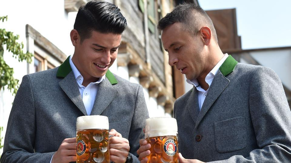 Bayern Munich's Colombian midfielder James Rodriguez (L) and defender Rafinha hold beer mugs as they pose during the traditional visit of members of German first division Bundesliga football club Bayern Munich at the Oktoberfest beer festival in Munich, Germany.  (AFP)