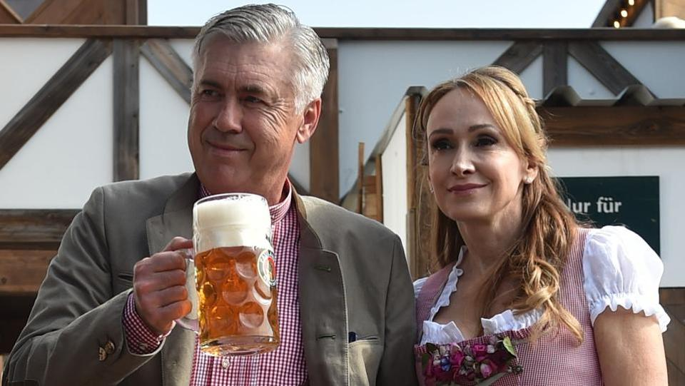 Carlo Ancelotti (L), Italian head coach of German first division Bundesliga football club FC Bayern Munich, holds a beer mug as he poses with his wife Mariann Barrena McClay during Bayern Munich's traditional visit at the Oktoberfest beer festival in Munich, Germany.  (AFP)