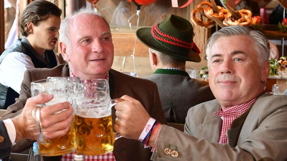 Bayern Munich's Italian head coach Carlo Ancelotti (R) and CEO Karl-Heinz Rummenigge clink glasses during the traditional visit of FC Bayern Munich to the Oktoberfest beer festival in Munich, Germany.  (AFP)