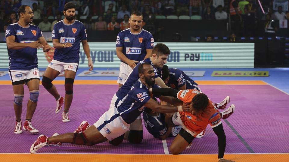 Dabang Delhi players pin down Puneri Paltan's Rajesh Mondal, in orange, during their Pro Kabaddi League match.