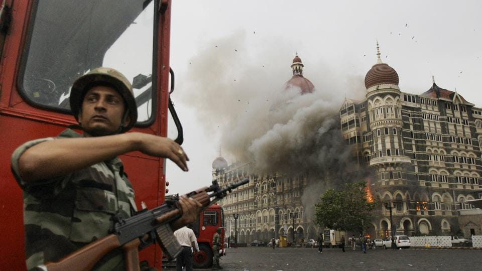 A soldier takes cover as the Taj Mahal hotel burns during the gun battle with militants in Mumbai in November 2008.