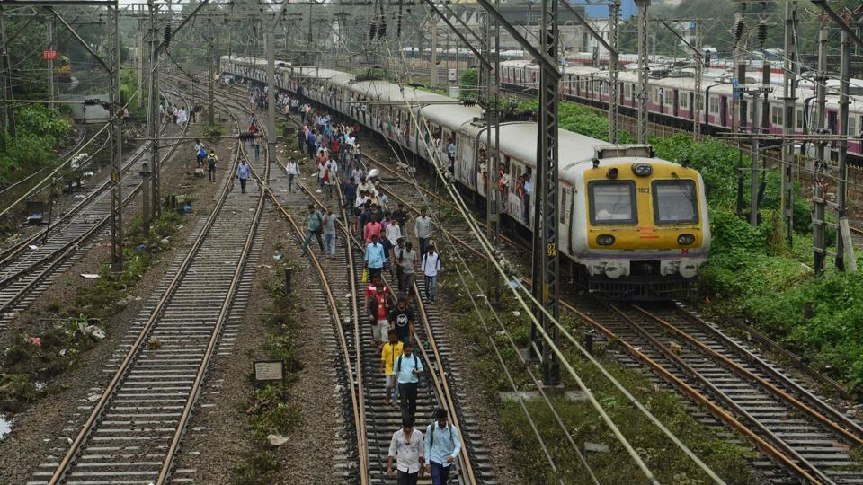 Commuters walk on railway tracks as train services slowly resume in Mumbai on August 30.