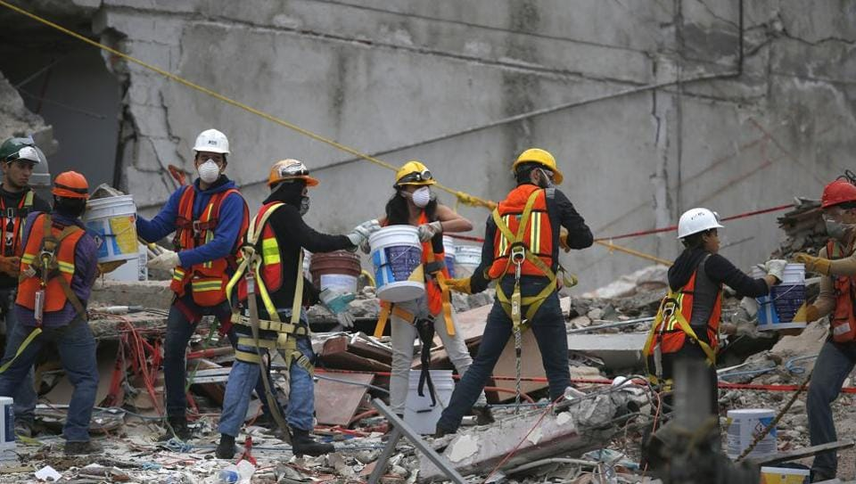 Search and rescue workers remove rubble a bucket at a time while standing on the debris of a felled office building brought down by a 7.1-magnitude earthquake, in the Roma Norte neighborhood of Mexico City, Sunday, Sept. 24, 2017.