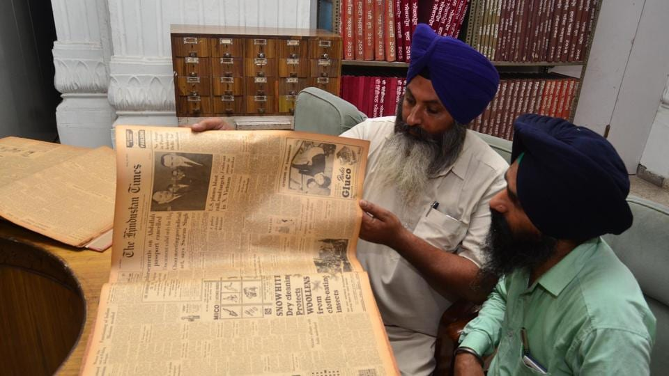 A researcher finding a piece of writing in a Hindustan Times edition from 1965 at Sikh Reference Library, Amritsar.