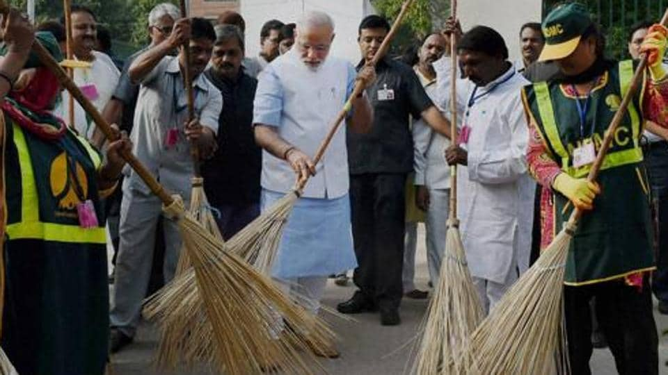 Prime Minister Narendra Modi wields a broom with New Delhi Municipal Corporation workers to launch 'Swachh Bharat Abhiyan' in Valmiki Basti in New Delhi in 2014.