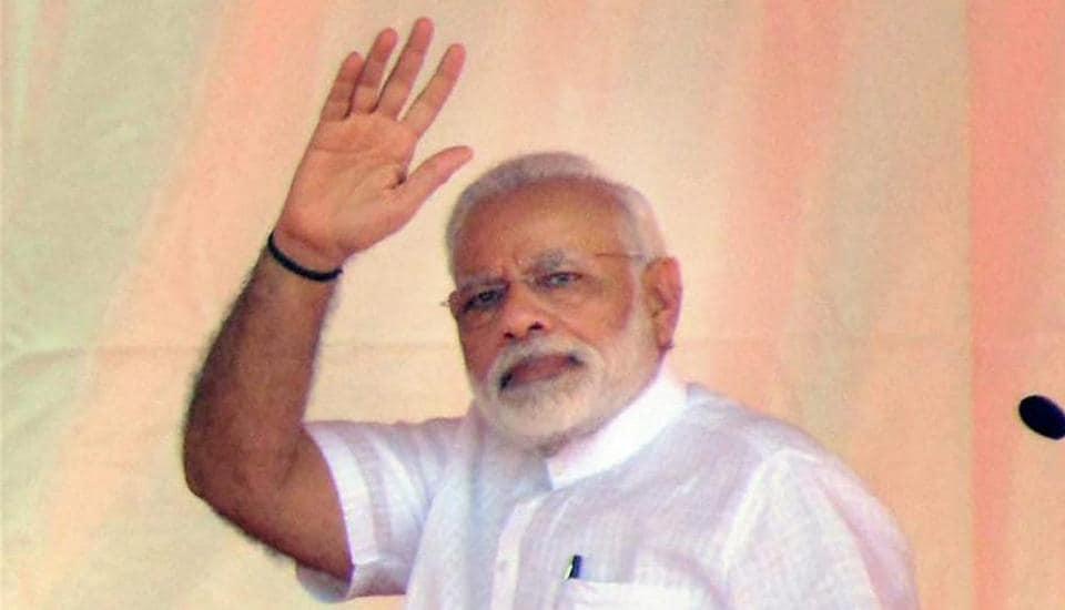 Prime Minister Narendra Modi waves at a crowd during the distributing the certificate to beneficiaries of the Pradhan Mantri Awas Yojana (Rural & Urban), in Varanasi.