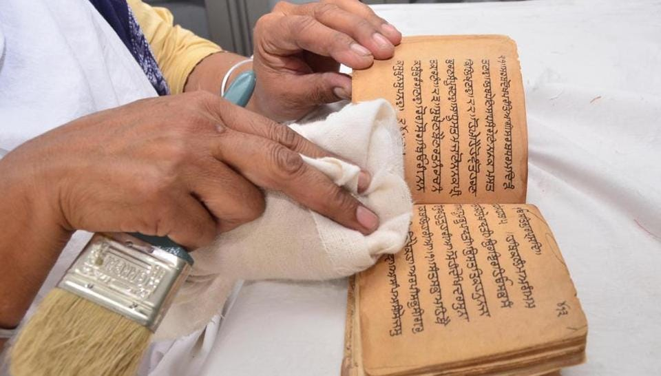 An employee cleaning a rare book for preservation at Sikh Reference Library in the Golden Temple complex on Sunday, September 24.