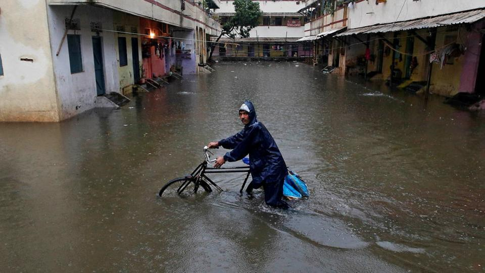 A delivery boy pushes his bicycle through a water-logged street after heavy rains at a residential colony in Mumbai, India (Shailesh Andrade / REUTERS)