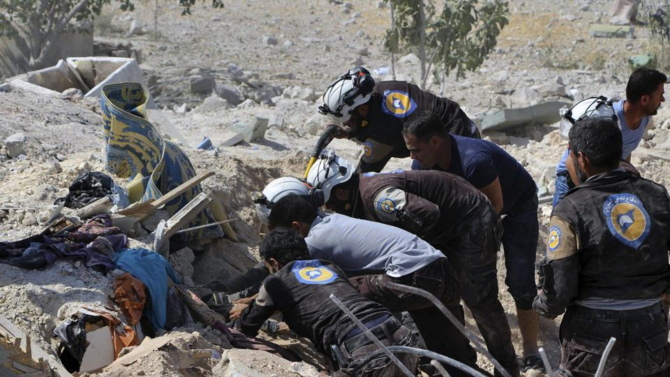 This photo provided by the Syrian Civil Defense White Helmets, shows civil defense workers searching through the rubble after airstrikes hit Khan Sheikhoun, in the northern province of Idlib, Syria, on Sunday.