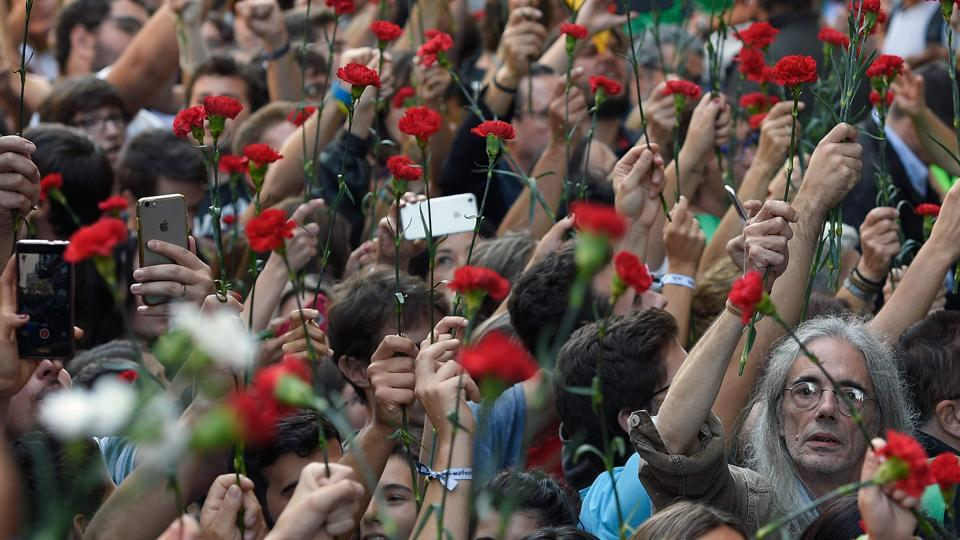 People hold flowers during a protest near the Economy headquarters of Catalonia's regional government in Barcelona on September 20, 2017. Thousands took to the streets of Barcelona as Spanish police detained 13 Catalan government officials in a crackdown ahead of an independence referendum which Madrid says is illegal. (Lluis Gene / AFP)