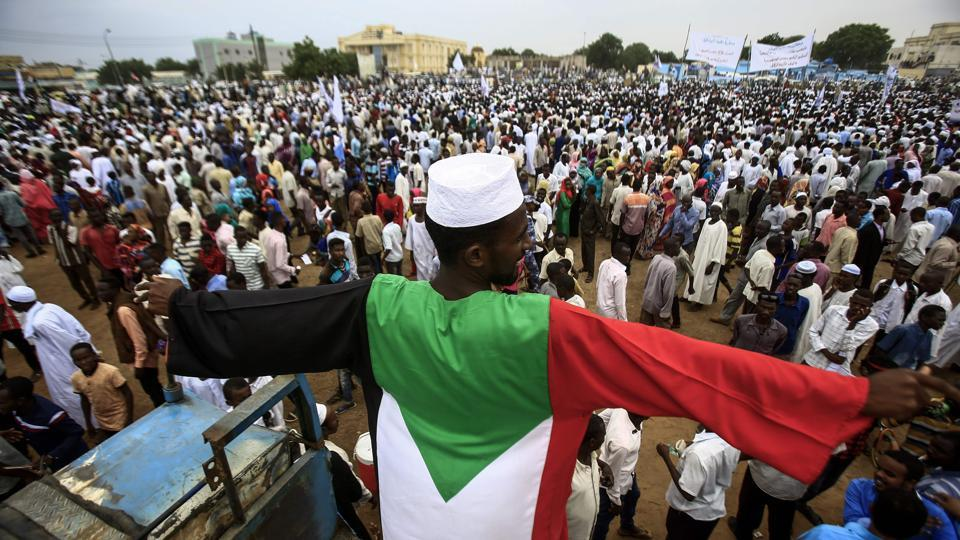 A man dressed in a garb coloured as the Sudanese national flag stands in a crowd gathered to receive President Omar al-Bashir (unseen) during his tour in Nyala, the capital of South Darfur province, on September 21, 2017.  (Ashraf Shazly  / AFP)