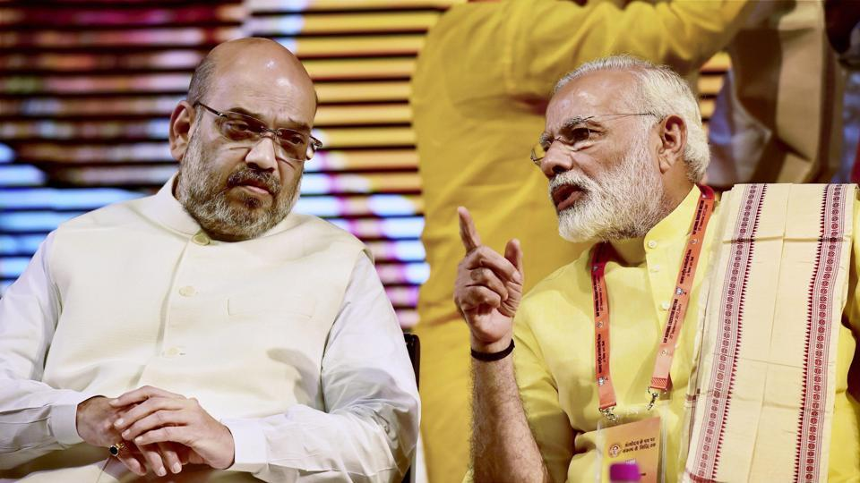 Prime Minister Narendra Modi speaks to BJP president Amit Shah during the party's national executive meeting at Talkatora Stadium,  New Delhi, on Monday.