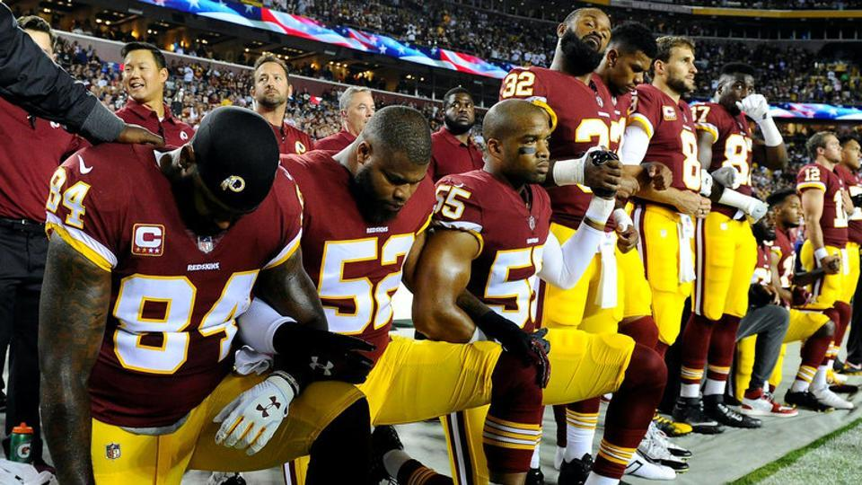 Washington Redskins tight end Niles Paul (84) and linebacker Ryan Anderson (52) kneel with teammates during the playing of the national anthem.
